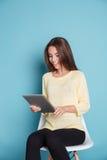 Mujer joven sonriente que mira la tableta Foto de archivo libre de regalías