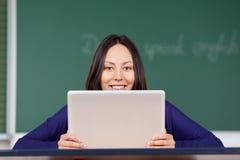 Mujer joven sonriente que mira sobre el ordenador portátil la escuela Fotos de archivo