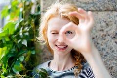 Mujer joven sonriente que muestra la muestra ACEPTABLE y la mirada de la cámara Fotografía de archivo libre de regalías