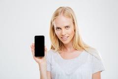 Mujer joven sonriente que muestra la pantalla en blanco del smartphone Imagenes de archivo