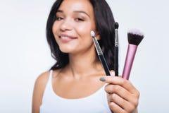 Mujer joven sonriente que muestra tres cepillos del maquillaje fotos de archivo
