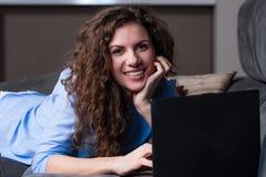 Mujer joven sonriente que pone en el sofá y usar el ordenador portátil imagen de archivo