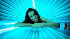 Mujer joven sonriente que pone en solarium Foto de archivo
