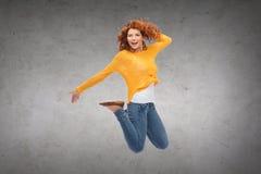 Mujer joven sonriente que salta en aire Imagen de archivo
