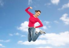 Mujer joven sonriente que salta en aire Imágenes de archivo libres de regalías
