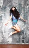 Mujer joven sonriente que salta en aire Imagenes de archivo