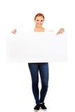 Mujer joven sonriente que señala para la bandera vacía Imágenes de archivo libres de regalías