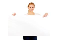Mujer joven sonriente que señala para la bandera vacía Imagenes de archivo