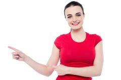 Mujer joven sonriente que señala a su derecha Foto de archivo