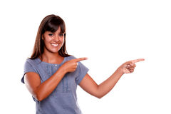 Mujer joven sonriente que señala a su izquierda Foto de archivo libre de regalías