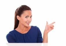Mujer joven sonriente que señala a su izquierda Fotos de archivo libres de regalías