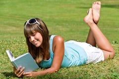 Mujer joven sonriente que se acuesta en hierba con el libro Fotos de archivo
