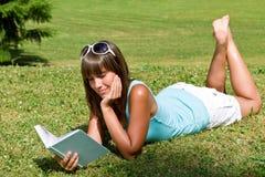 Mujer joven sonriente que se acuesta en hierba con el libro Imagen de archivo libre de regalías