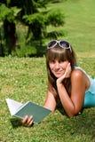 Mujer joven sonriente que se acuesta en hierba con el libro Imágenes de archivo libres de regalías