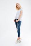 Mujer joven sonriente que se coloca con las manos en bolsillos de puntillas Foto de archivo libre de regalías