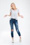 Mujer joven sonriente que se coloca con las manos en bolsillos de puntillas Imagenes de archivo