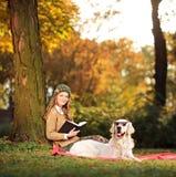 Mujer joven sonriente que se relaja con su perro Imágenes de archivo libres de regalías