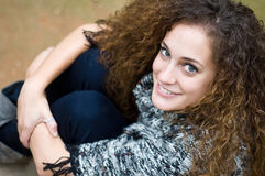Mujer joven sonriente que se sienta Imagen de archivo libre de regalías