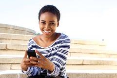 Mujer joven sonriente que se sienta afuera usando el teléfono móvil Foto de archivo