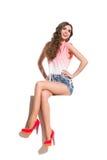 Mujer joven sonriente que se sienta con las piernas cruzadas Foto de archivo libre de regalías