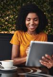 Mujer joven sonriente que se sienta en café usando la tableta digital foto de archivo libre de regalías