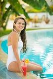 Mujer joven sonriente que se sienta en el borde de la piscina Imágenes de archivo libres de regalías