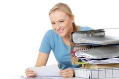 Mujer joven sonriente que se sienta en el escritorio Fotos de archivo