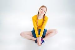Mujer joven sonriente que se sienta en el piso Fotografía de archivo