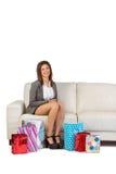 Mujer joven sonriente que se sienta en el sofá con los panieres Fotos de archivo