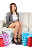 Mujer joven sonriente que se sienta en el sofá con los panieres Imagen de archivo