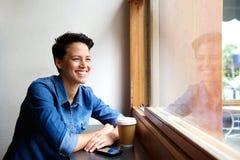 Mujer joven sonriente que se sienta en la cafetería que mira hacia fuera la ventana Imagenes de archivo