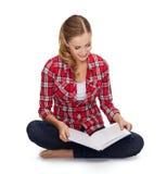 Mujer joven sonriente que se sienta en piso con el libro Imagen de archivo libre de regalías