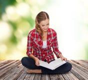Mujer joven sonriente que se sienta en piso con el libro Fotografía de archivo