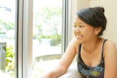 Mujer joven sonriente que se sienta por la ventana Imagen de archivo libre de regalías