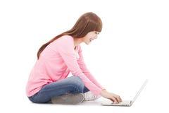 Mujer joven sonriente que se sienta y que mecanografía en un ordenador portátil Imagen de archivo libre de regalías