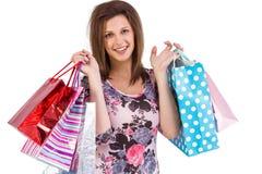 Mujer joven sonriente que sostiene bolsos de compras Foto de archivo libre de regalías