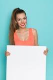 Mujer joven sonriente que sostiene el cartel blanco Imagen de archivo