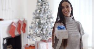 Mujer joven sonriente que sostiene hacia fuera un regalo de la Navidad almacen de metraje de vídeo