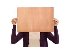Mujer joven sonriente que sostiene la hoja de madera en blanco Imágenes de archivo libres de regalías