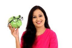 Mujer joven sonriente que sostiene la hucha Imagen de archivo libre de regalías