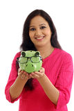 Mujer joven sonriente que sostiene la hucha Imagenes de archivo
