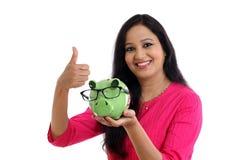 Mujer joven sonriente que sostiene la hucha Fotografía de archivo libre de regalías