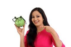 Mujer joven sonriente que sostiene la hucha - concepto de los ahorros Fotos de archivo