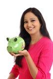 Mujer joven sonriente que sostiene la hucha - concepto de los ahorros Imagen de archivo