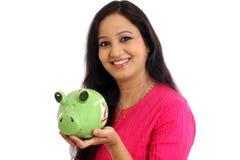 Mujer joven sonriente que sostiene la hucha - concepto de los ahorros Imagen de archivo libre de regalías