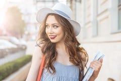 Mujer joven sonriente que sostiene los libros y que camina en la ciudad Foto de archivo libre de regalías