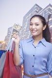 Mujer joven sonriente que sostiene muchos bolsos de compras, mirando la cámara Fotos de archivo