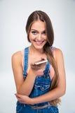Mujer joven sonriente que sostiene smartphone Foto de archivo libre de regalías
