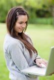 Mujer joven sonriente que sostiene su computadora portátil Foto de archivo libre de regalías