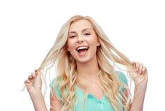 Mujer joven sonriente que sostiene su filamento del pelo Imágenes de archivo libres de regalías